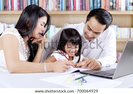 Cute little girl studying with her parents and a laptop on the table in the library