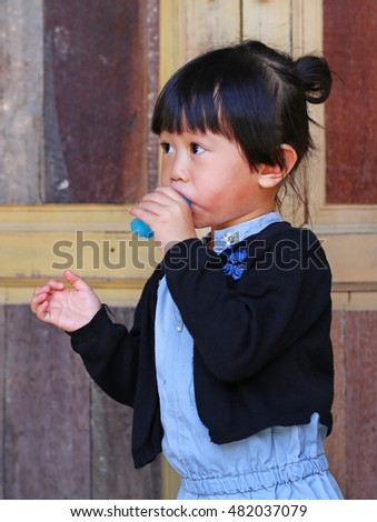 Cute little girl sucking lollipop. Tiny kid enjoying her sweet yummy popsicle.