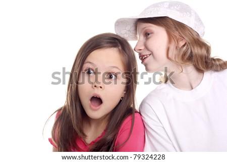 cute little girl surprised while her friend whispering something to her - stock photo