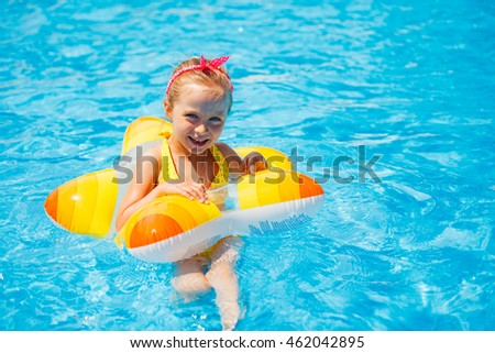 Cute little girl swimming in the pool in rubber ring, having fun in aquapark, happy summer holidays on the beach