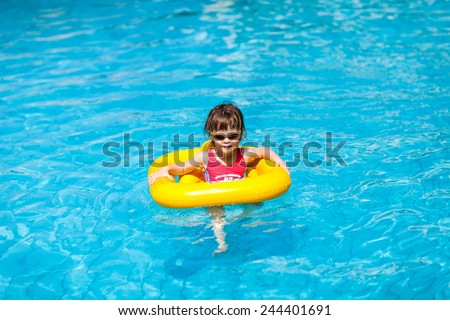 Cute little girl swims in a pool in a yellow life preserver - stock photo