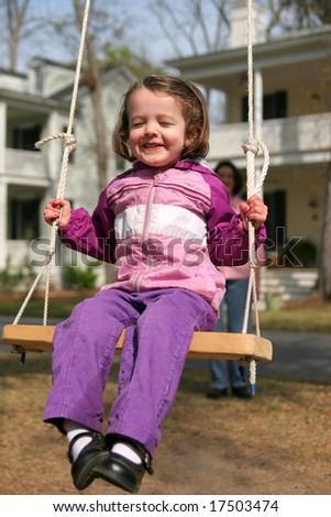 cute little girl swinging on rope swing, mom out of focus in background - stock photo