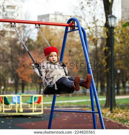 Cute little girl swinging on seesaw on children playground - stock photo