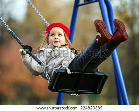 Cute little girl swinging on seesaw on children playground - stock photo