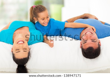 cute little girl tickling her father while family lying on bed at home - stock photo