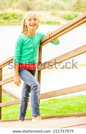 Cute little girl. Top view of cute little girl moving up by outdoor wooden stairs and smiling - stock photo