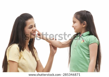 Cute little girl touching mother's nose over white background - stock photo