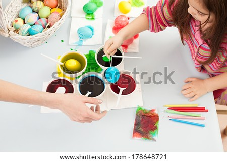cute little girl trying to dye the eggs for easter - stock photo