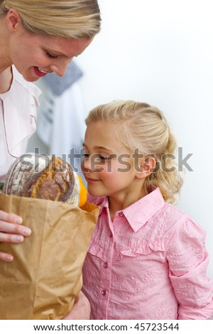 Cute Little girl unpacking grocery bag with her mother in the kitchen - stock photo