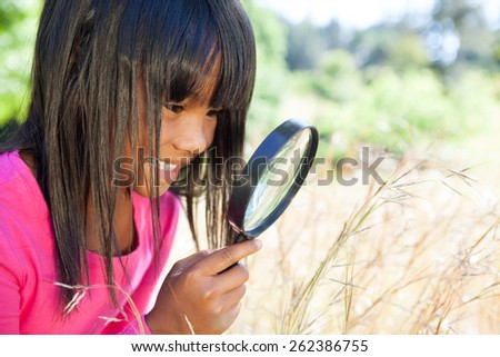 Cute little girl using magnifying glass in park on a sunny day - stock photo