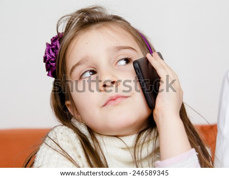 Cute little girl using modern smartphone - stock photo