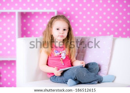 Cute little girl using modern tablet computers on white sofa in the polka-dot bright pink room at home fun game alone - stock photo