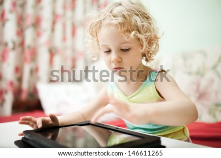Cute little girl using tablet computer