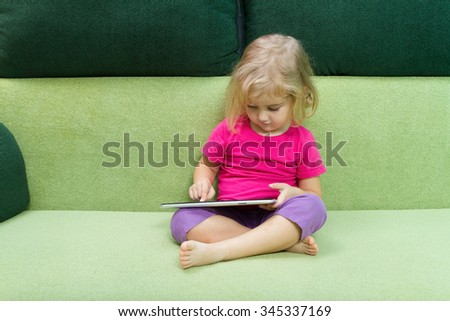 Cute little girl using tablet computer sitting on a green couch. - stock photo