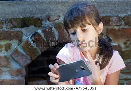 cute little girl using the phone and takeing selfie