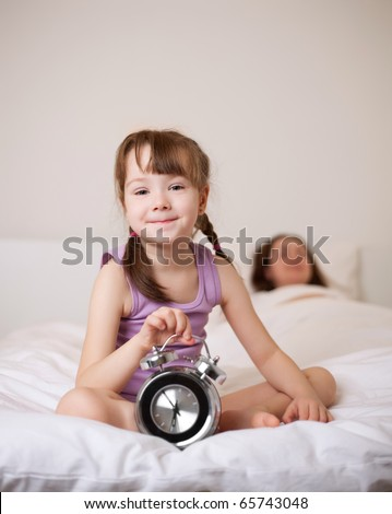 cute little girl waking up in the morning and switching off the alarm clock, her mother sleeping on the background (focus on the child) - stock photo