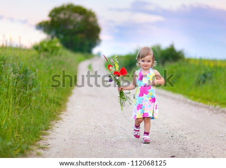 Cute little girl walking on the road with bouquet of flowers - stock photo