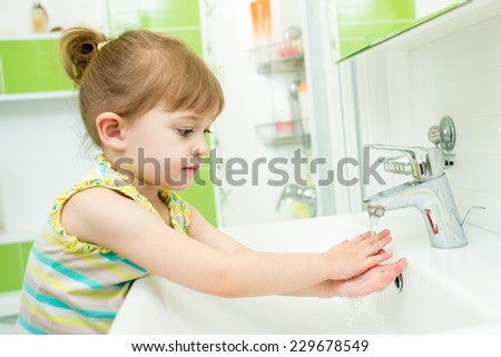 Cute little girl washing hands in bathroom - stock photo