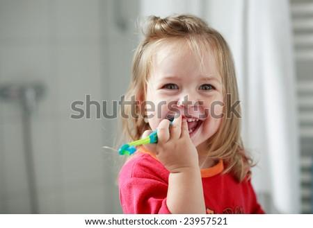Cute little girl washing her teeth - stock photo
