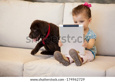 Cute little girl watching a movie on her tablet computer while her dog keeps her company