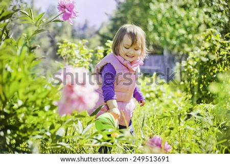 Cute little girl watering flowers in the summer garden