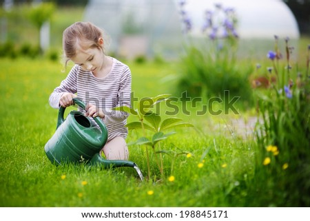 Cute little girl watering plants in the garden - stock photo
