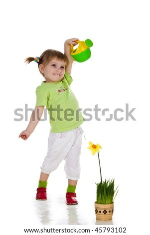 Cute little girl watering the flower. Studio shot