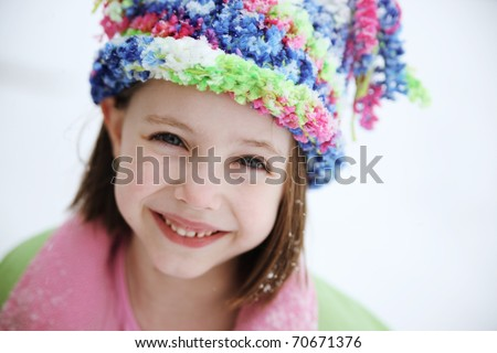 Cute little girl wearing a winter hat and coat outside in the cold snow - stock photo