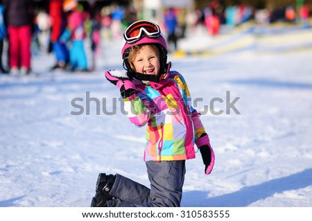Cute little girl wearing a winter jacket and a ski helmet throwing a snowball and smiling