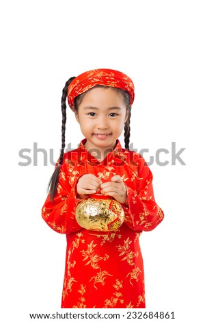 Cute little girl wearing ao dai dress, holding golder lantern