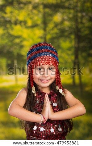 Cute little girl wearing beautiful red dress with matching pearl hat, posing for camera, green forest background