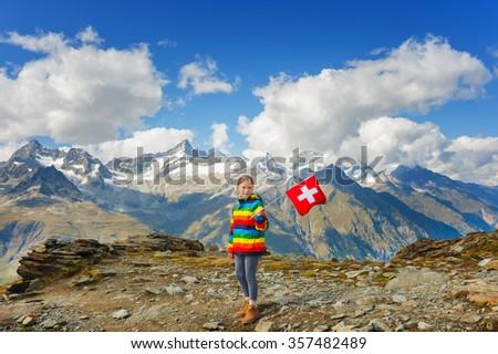 Cute little girl wearing bright rainbow colored coat, holding swiss flag, standing in front of Gornergrat glacier, Switzerland - stock photo