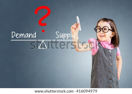 Cute little girl wearing business dress and writing demand and supply compare on balance bar. Blue background. - stock photo