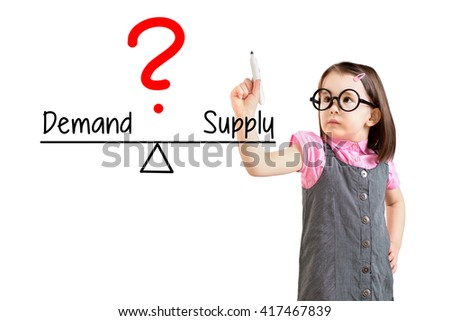 Cute little girl wearing business dress and writing demand and supply compare on balance bar. White background. - stock photo