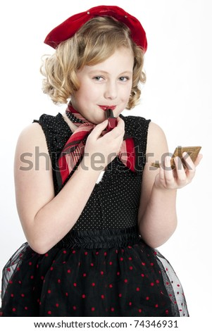 Cute little girl wearing dress putting on red lipstick - stock photo