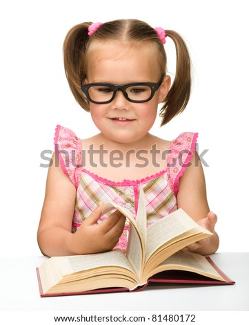 Cute little girl wearing glasses is flipping over pages of a book, isolated on white - stock photo