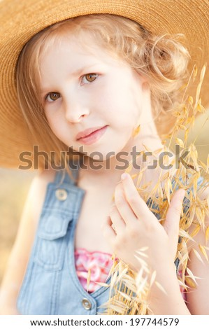 Cute little girl wearing hat outdoors - stock photo