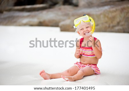 Cute little girl wearing mask and snorkel on white tropical beach - stock photo