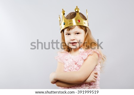 Cute little girl wearing pink dress and metal golden crown, looking at camera, gray studio background, copy space, portrait. - stock photo