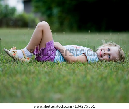 Cute little girl wearing purple shorts and blue striped shoes with flowered sandals laying in grass and smiling - stock photo