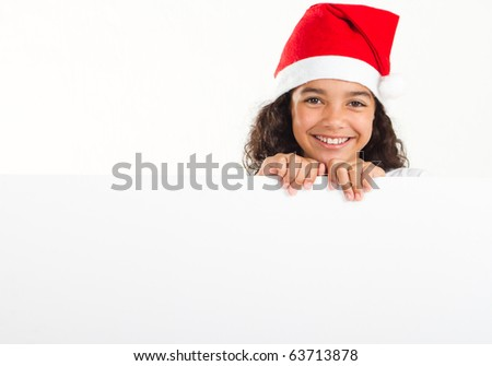 cute little girl wearing santa hat and holding a white board - stock photo