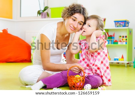 Cute little girl whispering to her mother during Easter eggs painting - stock photo