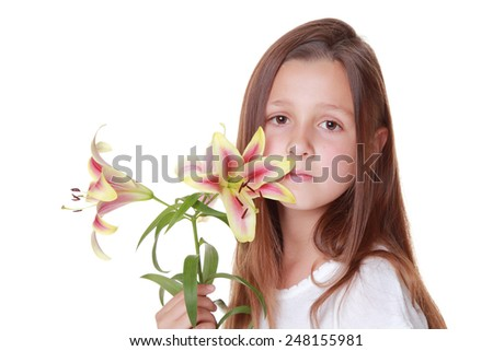 Cute little girl with a beautiful smile with long hair holding a fresh tender lilies isolated on white on Beauty and Fashion - stock photo