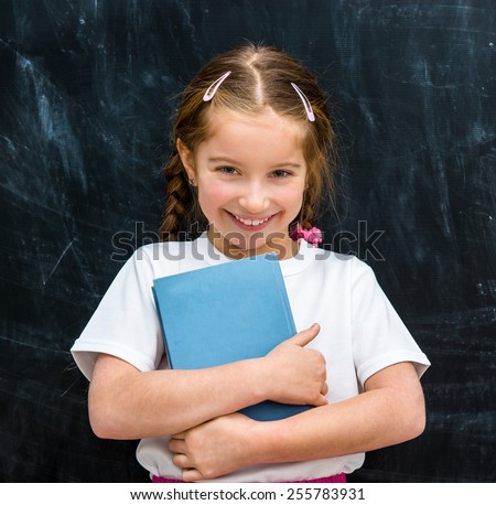 cute little girl with a blue book in hands smiling on the background of the school board - stock photo