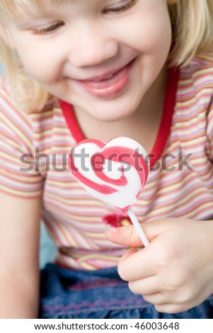 Cute little girl with a heart shape lollipop