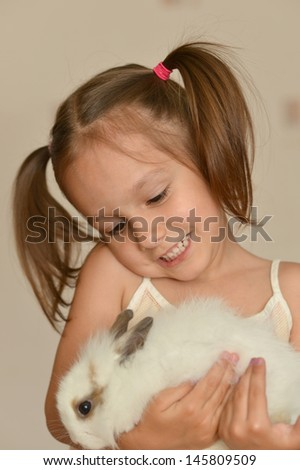 Cute little girl with a rabbit at home