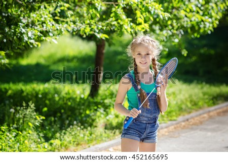 Cute little girl with a racket in his hand standing in the sunny summer park