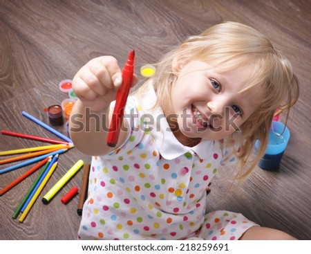Cute little girl with a red marker in hand draws. - stock photo