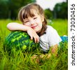 cute little girl with a watermelon on the grass in summertime - stock photo