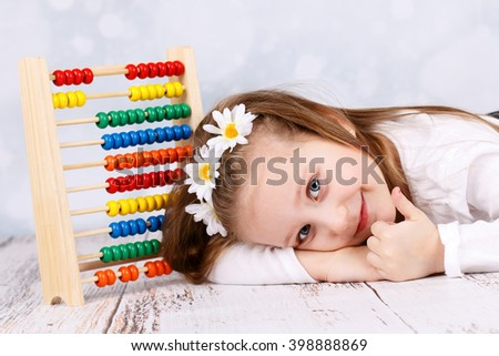 Cute little girl with abacus - stock photo